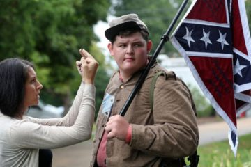 woman flipping her middle fingers in front of a young man holding a confederate flag